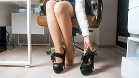 Closeup image of young businesswoman taking off high heels shoes at office royalty free stock image