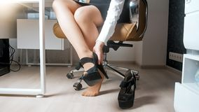 Closeup photo of young businesswoman taking off high heels shoes under table stock image