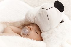 Closeup photo of sleeping baby with bear stock photography