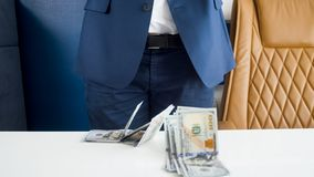 Closeup image of stack of money lying on office desk in front of businessman in blue suit stock photos