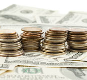 Closeup photo of stacks coins over dollars Stock Photography