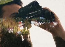 Closeup photo of stylish bearded traveler staring through binoculars. Double exposure, beautiful mountain landscape background. Made in vintage style Stock Images