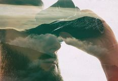 Closeup photo of stylish bearded traveler staring through binoculars. Double exposure, beautiful mountain landscape background. Made in vintage style Royalty Free Stock Images
