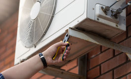 Closeup photo of technician installing outdoor air conditioning. Closeup photo of male technician installing outdoor air conditioning unit Royalty Free Stock Image