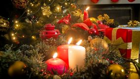 Closeup image of three burning candles against glowing colorful Christmas lights Stock Photography