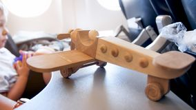 Closeup image of toy airplane against little boy sitting in passenger seat at illuminator stock photo