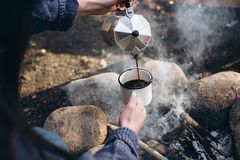 Closeup photo of traveler`s hand pours itself hot beverage in mountains near to bonfire. A young tourist woman drinks a hot drink from a cup and enjoys nature royalty free stock photography