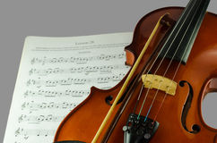 Closeup photo of violin and bow. On note sheet with text space Royalty Free Stock Image