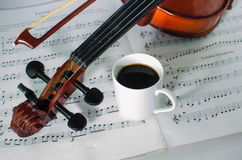 Closeup photo of violin and cup of coffee. Closeup photo of violin and coffee on note sheet with text space Stock Photography
