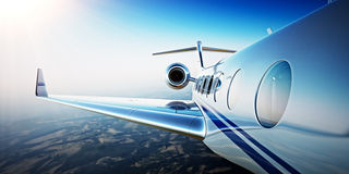 Closeup Photo of White Luxury Generic Design Private Aircraft Flying in Blue Sky at sunrise.Uninhabited Desert Mountains Stock Photos