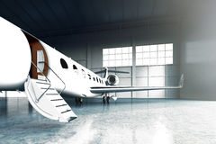 Closeup photo of White Matte Luxury Generic Design Private Jet parking in hangar airport. Concrete floor. Business Royalty Free Stock Photography