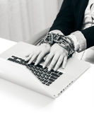 Closeup photo of woman locked to laptop by chain Stock Photo