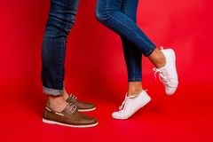 Closeup photo of woman and man legs in jeans, pants and shoes, g. Closeup photo of women and men legs in jeans, pants and shoes, girl with raised leg, stylish stock photos