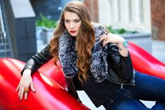 Closeup Photo of Woman Wearing Black Leather Fur-lined Jacket and Blue Denim Bottoms Stock Photo
