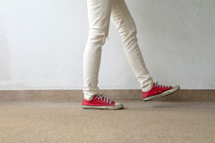 Closeup Photo of From Woman Wearing Red Sneakers On The Concrete Floor Background. Great For Any Use Royalty Free Stock Image