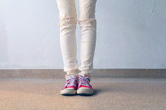 Closeup Photo of From Woman Wearing Red Sneakers On The Concrete Floor Background. Great For Any Use Stock Photos