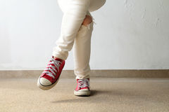 Closeup Photo of From Woman Wearing Red Sneakers On The Concrete Floor Background. Great For Any Use Stock Photography