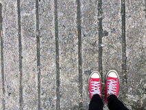Closeup Photo of From Woman Wearing Red Sneakers On The Concrete Floor Background. Great For Any Use Stock Image