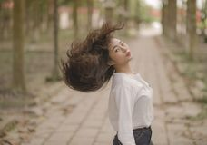 Closeup Photo of Woman in White Crew-neck Long-sleeved Shirt Shaking Her Hair in the Middle on Road Stock Images