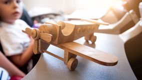 Closeup image of wooden airplane miniature against little boy sitting in passenger seat during flight royalty free stock image