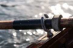 Closeup photo of wooden paddle attached to boat used for rowing in the water, lake Bled on a sunny day. Closeup photo of wooden paddle used for rowing in the stock photos