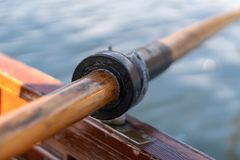 Closeup photo of wooden paddle attached to boat used for rowing in the water, lake Bled on a sunny day. Closeup photo of wooden paddle used for rowing in the stock photo