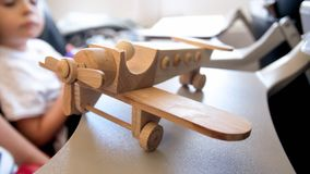 Closeup image of wooden toy plan against little boy sitting in airplane seat royalty free stock photo