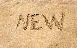 Closeup photo of word New written on sandy beach Royalty Free Stock Image