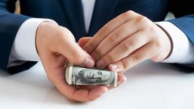 Closeup image of young businessman holding big stack of money in hands. Closeup photo of young businessman holding big stack of money in hands stock photo