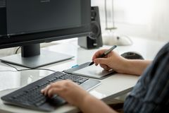 Closeup image of young man designer siting behind computer and working with graphic tablet. Closeup photo of young man designer siting behind computer and Stock Photos