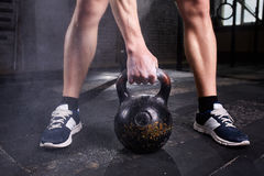 Closeup photo of young man`s legs in sneackers and arm while keeping kettlebell against dark background. Stock Image
