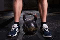 Closeup photo of young man`s legs in sneackers and kettlebell against dark background. Royalty Free Stock Photography