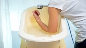 Closeup photo of young woman checking water temperature in baby bathtub with elbow. Closeup image of young woman checking water temperature in baby bathtub with royalty free stock photo