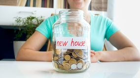 Closeup photo of young woman with jar full of money savings for buying new house. Closeup image of young woman with jar full of money savings for buying new stock images