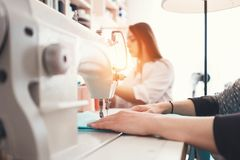 Closeup photo of young woman`s hands seamstress sitting and sews on sewing machine in creative designer studio. Two young businesswoman dressmaker making new Stock Photo