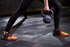 Closeup photo of young woman`s legs in leggings and sneackers and kettlebell against dark background. Royalty Free Stock Photos