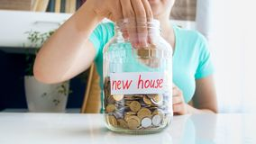 Closeup photo of young woman throwing coin in glass jar with savings for buying new house. Closeup image of young woman throwing coin in glass jar with savings royalty free stock images