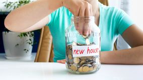 Closeup photo of young woman throwing money in glass jar with savings for buying new house. Closeup image of young woman throwing money in glass jar with savings royalty free stock photography