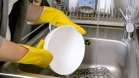 Closeup photo of young woman washing dishes in kitchen sink. Closeup image of young woman washing dishes in kitchen sink stock images