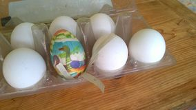 A closeup photograph of a single painted plastic Easter egg nested inside of a plastic egg carton with several real chicken eggs stock photo