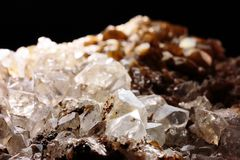 Closeup photograph of white and brown quartz. Stone lit from above with very small part of black background. Natural phenomenon. Mountain or rock crystal Royalty Free Stock Photography