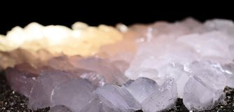 Closeup photograph of white translucent calcite. Stone with yellow details, lit from inside with very small part of black background. Natural phenomenon Stock Photo
