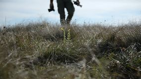 Closeup of a photographer`s foot whose silhouette goes beyond the horizon into defocus. A photographer walks across a. Field of wild grass stock video footage