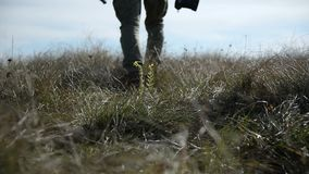 Closeup of a photographer`s foot whose silhouette goes beyond the horizon into defocus. A photographer walks across a. Field of wild grass stock footage