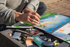 Closeup photos of street atrist, painting on a street park. Art in a big city. Kiev, Ukraine. Editorial photo. Stock Image