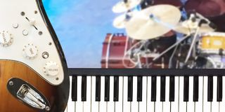 Closeup on Piano keyboard and electric guitar musical instrument. With Golden cymbal and drum set on stage background Royalty Free Stock Image
