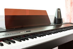 Closeup piano keyboard with metronome background. Royalty Free Stock Photography