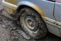Grey van has its tires full of clay from driving on a wet clay road - 1/2 stock images