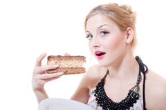 Closeup picture of blue eyes beautiful blond young woman having fun eating alone large chocolate cake happy smiling stock photo