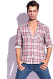 Man holds thumbs in pockets. Closeup picture of a casual young man holding his hands in his pockets. isolated on white background Royalty Free Stock Image